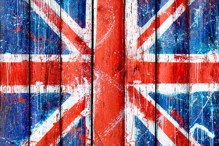 塗られた木製の壁や英国の旗の落書きにフェンス。ユニオン ジャックのパターンで自然木の板。イギリスのグランジ旗と抽象的なテクスチャ背景