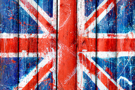 Painted wooden wall or fence with graffiti of British flag. Natural wooden boards with pattern of Union Jack. Abstract textured background with grunge flag of United Kingdom Фото со стока