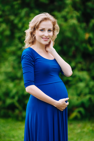 Portrait of lovely smiling young pregnant woman in blue dress with long blond curly hair holding her belly and looking at camera in summer park. Pregnancy and femininity concept. Mother's Day