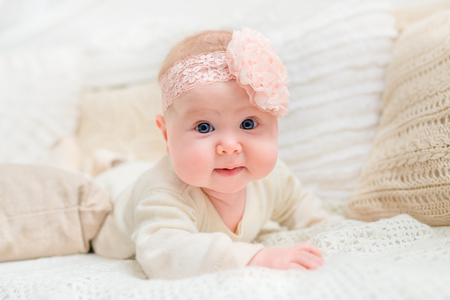 babyhood: Smiling baby girl with chubby cheeks and big blue eyes wearing white clothes  and pink band with flower lying on bed and looking at camera. Babyhood and childhood concept