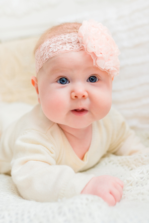babyhood: Amazed baby girl with chubby cheeks and big blue eyes wearing white clothes and pink band with flower lying on bed. Babyhood and childhood concept Stock Photo