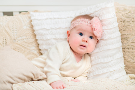 babyhood: Surprised beautiful baby girl with chubby cheeks and big blue eyes wearing white clothes and pink band with flower lying on bed with knitted pillows. Babyhood and childhood concept Stock Photo
