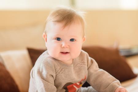 ブロンドの髪と青い目のソファの上に座って、カメラ目線のニット セーターを着て笑顔の小さな子供の肖像画。幸せな子供時代 写真素材