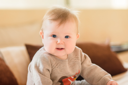 Portrait of smiling little child with blond hair and blue eyes wearing knitted sweater sitting on sofa and looking at camera. Happy childhood