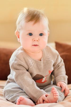 かわいらしい子供ブロンドの髪と青い目身に着けているニットのセーターのソファーに座っていると、彼女の足に触れます。幸せな子供時代 写真素材