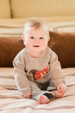 ブロンドの髪と青い目を着て笑っている小さな子供ニット セーターのソファーに座っていると、彼女の足に触れます。幸せな子供時代