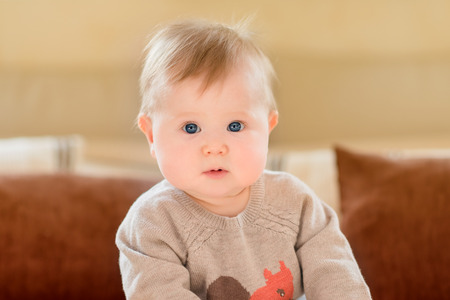 ブロンドの髪と青い目のソファの上に座って、カメラ目線のニット セーターを着てびっくり小さな子供の肖像画。幸せな子供時代 写真素材