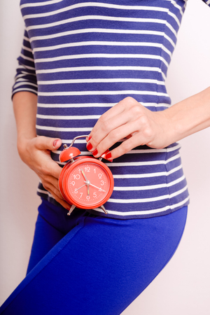 cystitis: Young woman in striped shirt holding red alarm clock feeling pain or hunger in stomac. Over white background Stock Photo