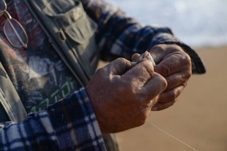 hand line fishing: Hand holding a fish caught on a fishing line in lake.