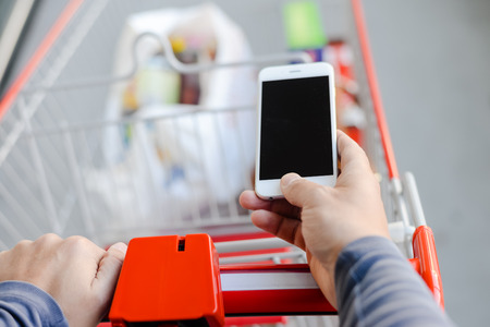Closeup on person holding mobile phone in hand during shopping. Cart on store background Фото со стока
