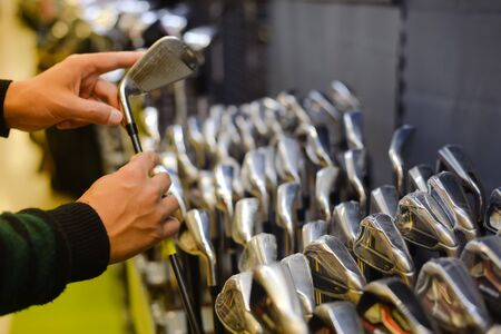 gamme de produit: Closeup photo of person holding in hand golf club at a Golf Shop.