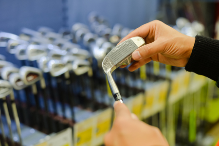 gamme de produit: Person holding in hand club at a golf shop. Closeup photo of choice concept Banque d'images