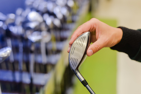 Person holding in hand golf club at a Golf Shop. Closeup photo