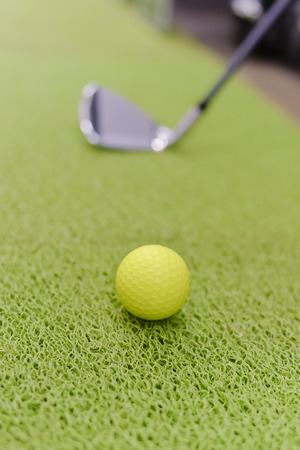 carpet grass: Playing indoors. Golf club and ball on green carpet grass background texture Stock Photo