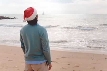 holidaymaker: Man in santa hat on the beach background. Christmas vacation. Stock Photo