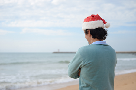 holidaymaker: Santa Claus sunbathing at the beach. Christmas or New Year travel destinations vacation concept