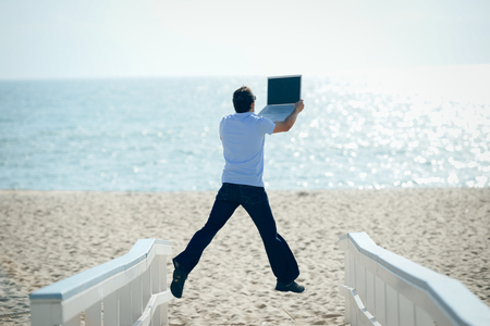 flying man: Happy jumping businessman working with computer on the beach background. Back view of flying man holding laptop on sea vacation