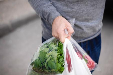 男性が買い物の後彼の手で袋を運ぶします。果物や野菜の完全な袋のクローズ アップ。 写真素材