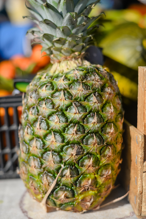 roadside stand: Whole pineapple standing on a table background of market stand