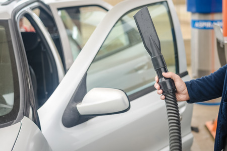 domestic garage: Closeup on auto car service cleaning and vacuuming interior. Close up on hand