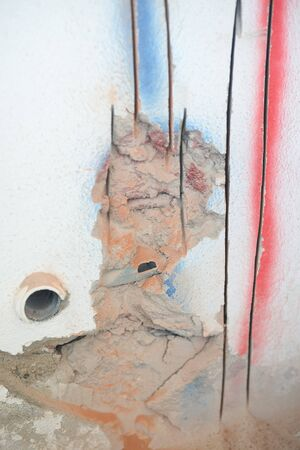 exposed concrete: Closeup on concrete wall with exposed socket, repair procedure