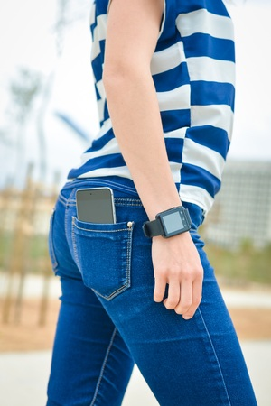 Closeup on hand smart watch and cell phone in back pocket of female jeans