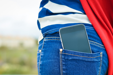 Closeup on cell phone in back pocket of female jeans