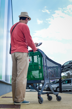 Person walking holding mobile smart phone in hand during shopping. Cart on store car park background. Back side view