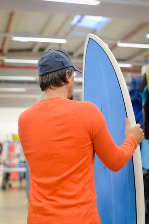 surf shop: Back view of male surfer holding a surf board on shop background indoors Stock Photo