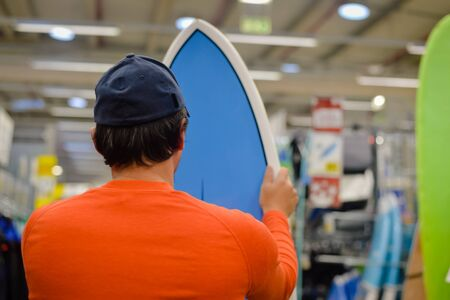 surf shop: Man choosing and holding a blue surf board on shop or factory background indoors. Back view