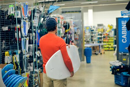 surf shop: Man choosing and holding a white surf board on shop background indoors