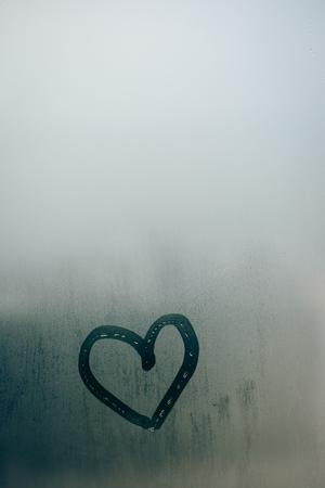 ガラスに描かれたハートが大好きです。ウィンドウがバック グラウンドに滴と曇った 写真素材