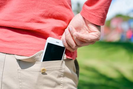 屋外の日当たりの良い背景にバック ポケットにスマート フォンを取る持っている男の手のクローズ アップ 写真素材