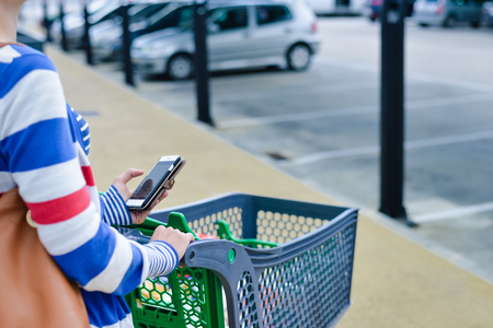 Closeup on person holding mobile smart phone in hand during shopping. Cart on store parking background shopping