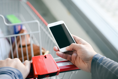 Cellphone screen and cart on store goods background. Closeup on person holding mobile smart phone in hand during shopping.