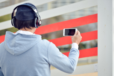 selfy: Watching video, taking selfy photo. Backview of man with headphones holding mobile smart phone on outdoors background. Stock Photo