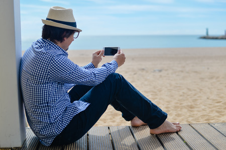 barefoot man: Person sitting using mobile smartphone, seaside background. Back side view picture of barefoot man on blue sky outside terrace seashore Stock Photo
