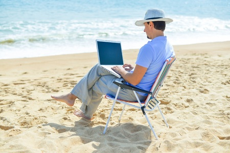 Back side view of relaxed man using laptop, beach background, outside sunny summertime