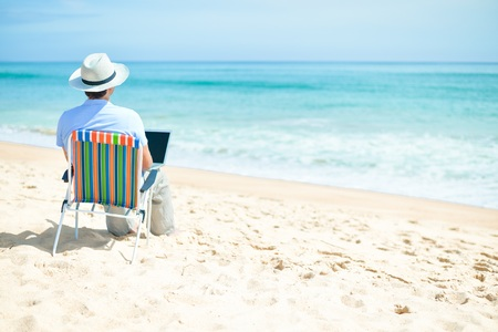 Handsome relaxed man using laptop, beach background, back side view outside