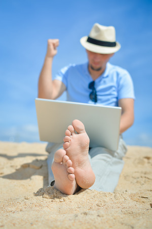 Happy business man in hat working using notebook computer on the beach blue sky background outside. Hand up with thumb up finger