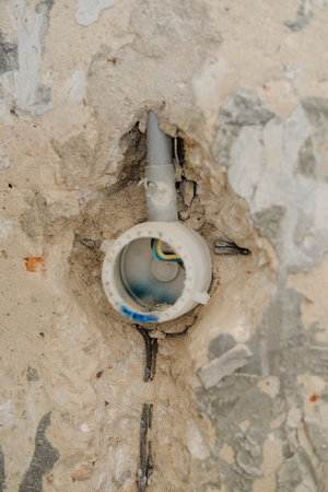 wall socket: Closeup on concrete wall with exposed wires in wall socket, repair procedure