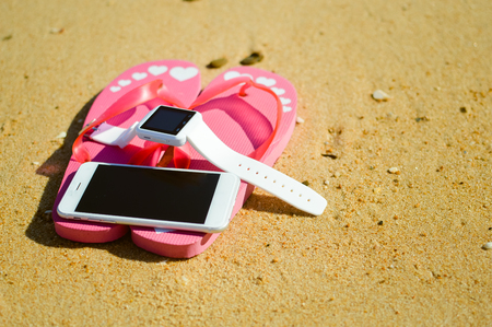 flipflops: Closeup on smart watch phone and flip-flops on beach background. Top view style, outside fun for photo and video for journey Stock Photo
