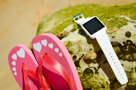 oudoors: Closeup on smart watch phone and flip-flops on beach background. Top view style, outside fun for photo and video for journey Stock Photo