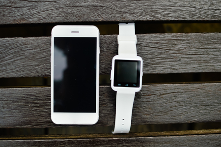hand lay: Hand smart watch smart phone, wooden surface outside background, Top view mock up flat lay design