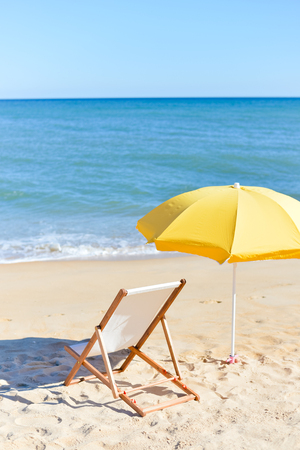 Back View Of Deckchair, Sun Lounger Under Umbrella On Sand Beach.