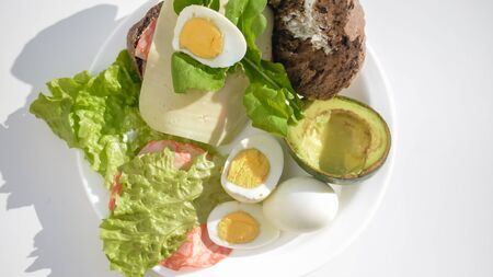 avacado: Avacado, bread, bacon and egg with salad in plate on table, closeup top view flat lay Stock Photo