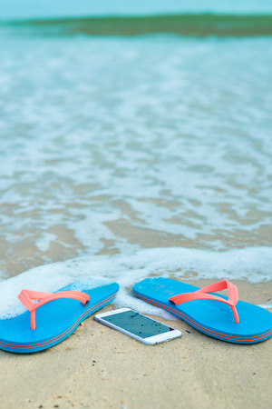 flip phone: Top view on mobile phone with flip flops on sandy summer beach background. Happy joyful vacation close up Stock Photo