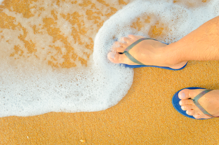 Top view close up of person walking along tropical exotic ocean beach wearing blue flip flops