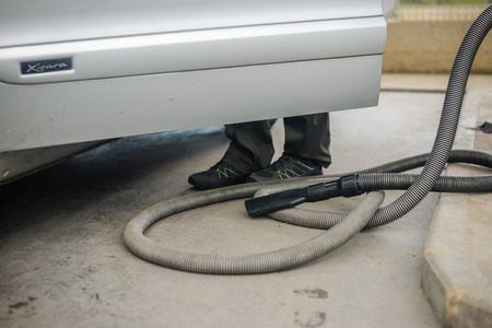 rinse spray hose: Car servicing and cleaning on the driveway, closeup