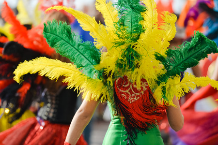 Back view of carnaval queen at carnival parade with colorful feathers. closeup photo
